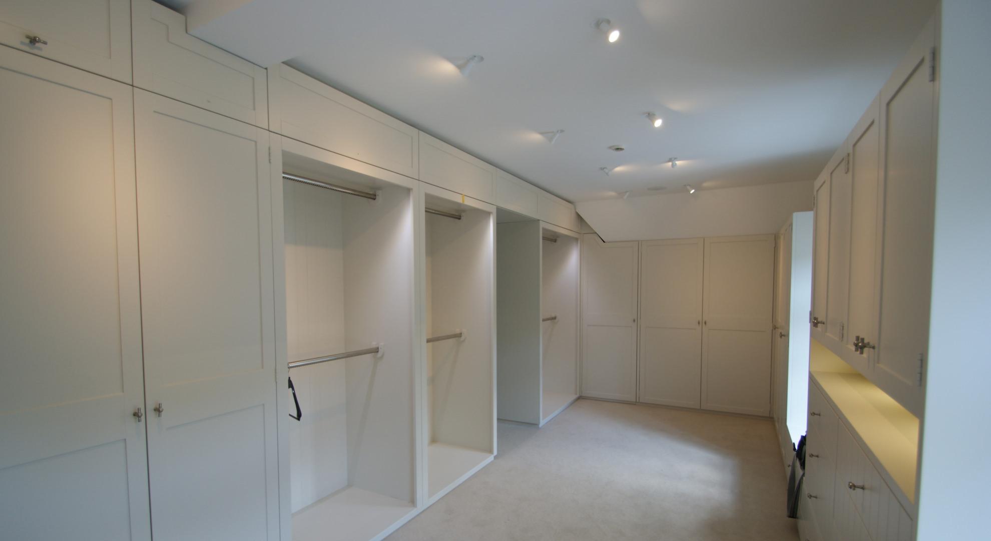 Ankleidezimmer mit offenen und geschlossenen Bereichen in Mattlack