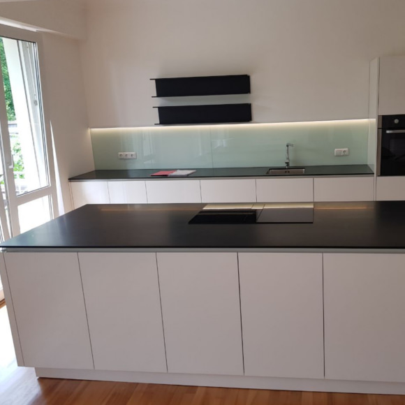 Schöne Küche mit Insel in Corian schwarz und Front weiß hochglanz