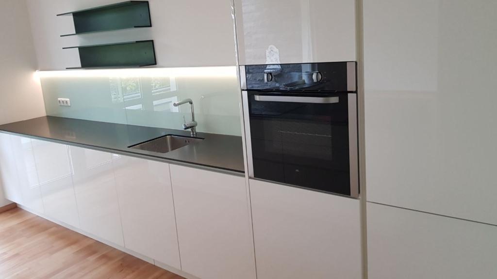 Küchenzeile in weiß Hochglanz mit schwarzer Arbeitsplatte aus Corian mit Glasrückwand