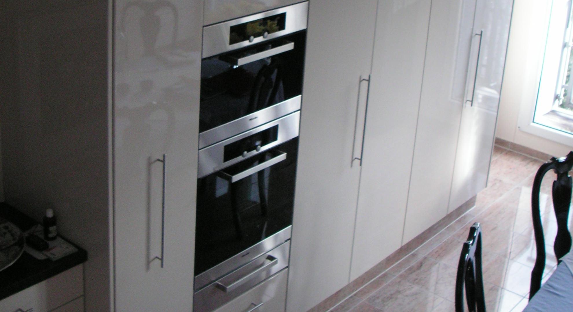 Küchenschrank mit Geräten und verdeckter Arbeitsplatte hinter Falttüren