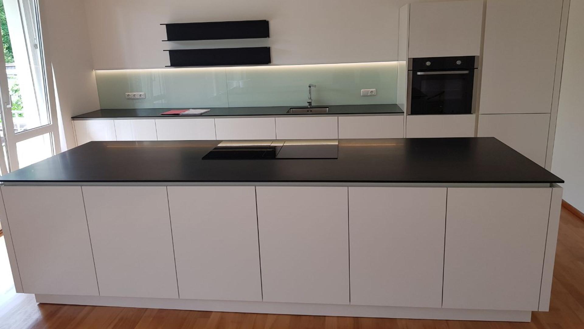 Wunderschöner Küchenblock mit Corian schwarz, hoch glänzend weiße Fronten